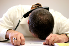 man slumped on desk with phone on his head