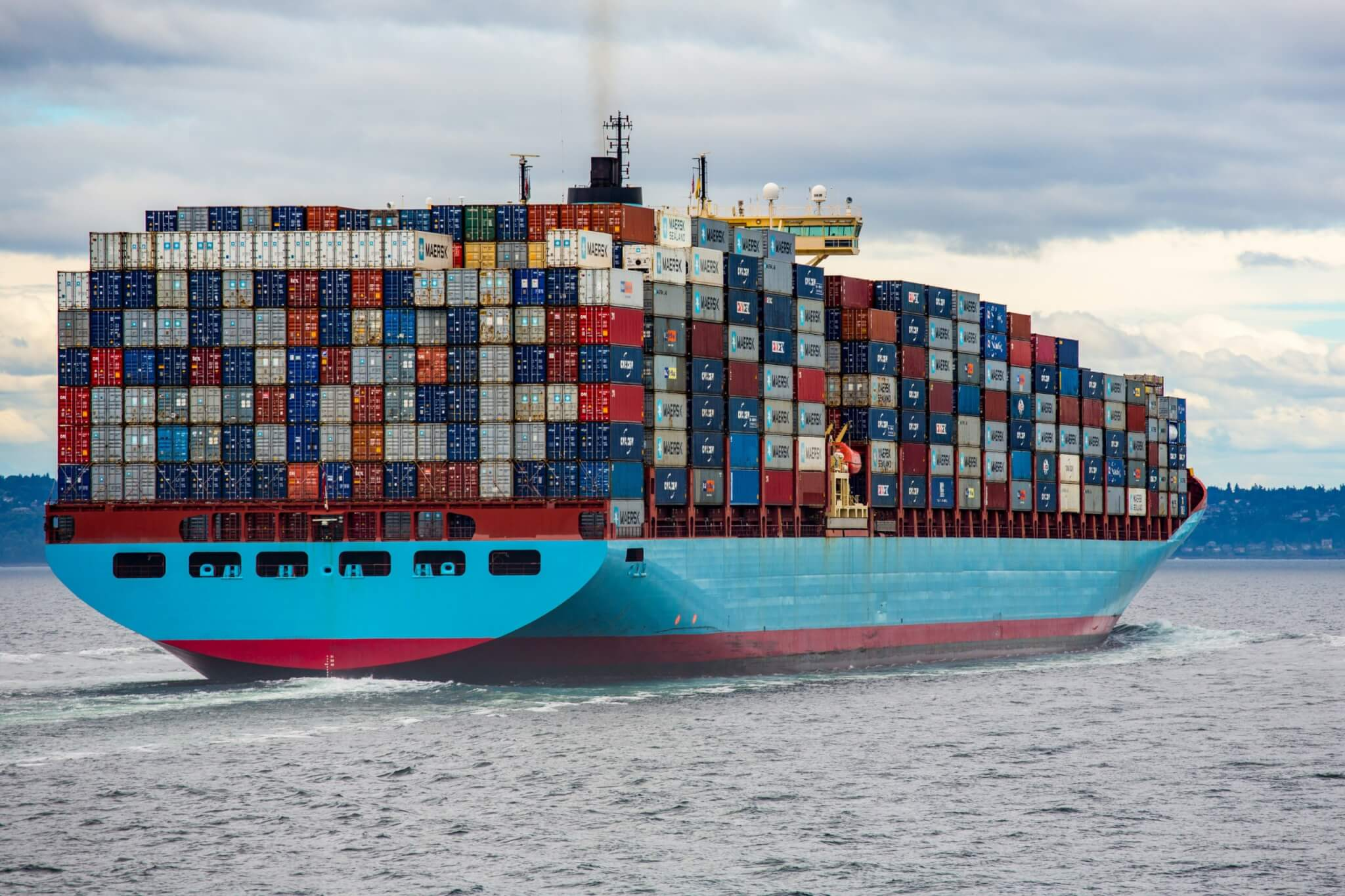ship carrying shipping containers contributing to supply chain
