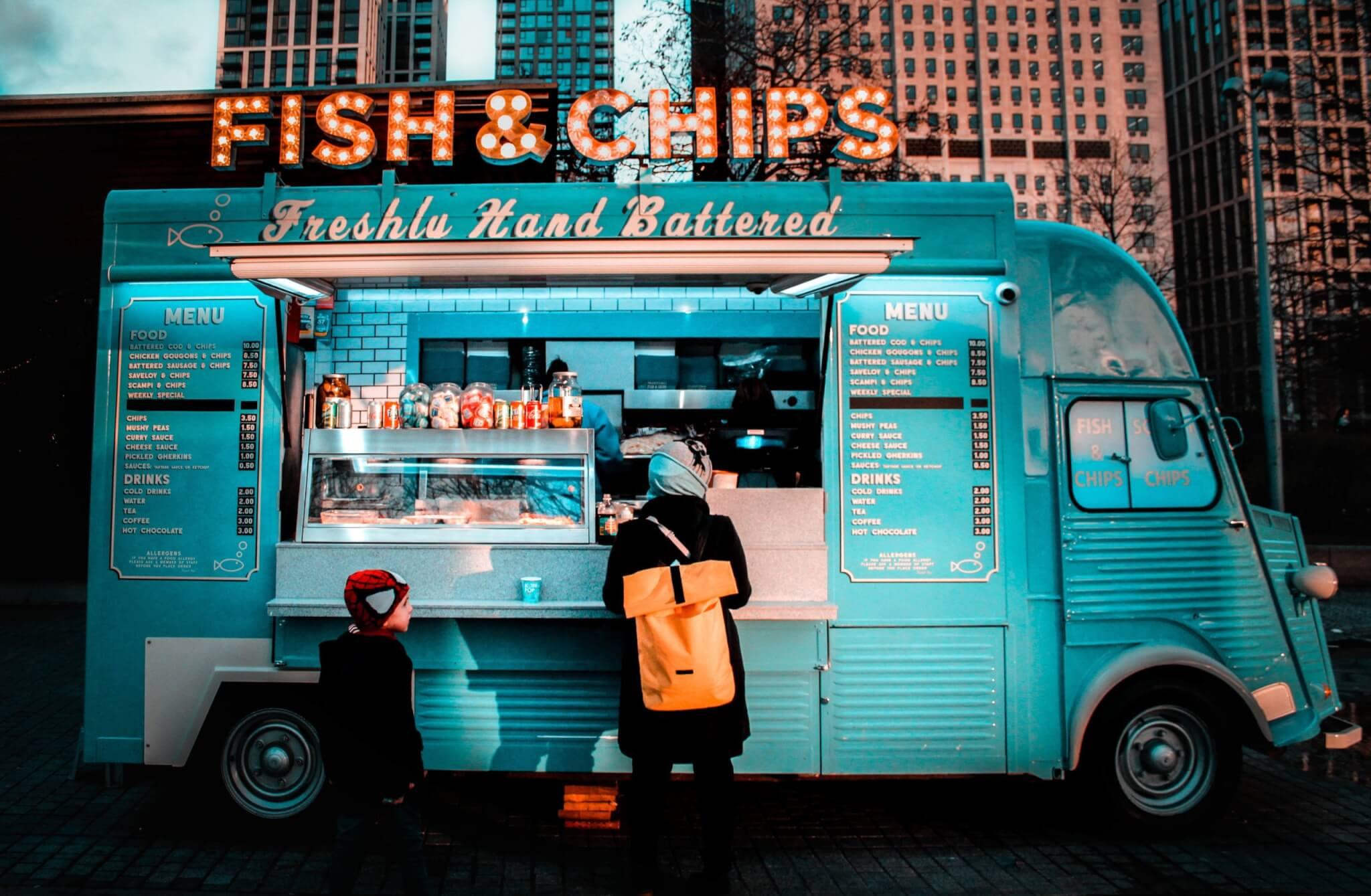teal food truck serving a customer