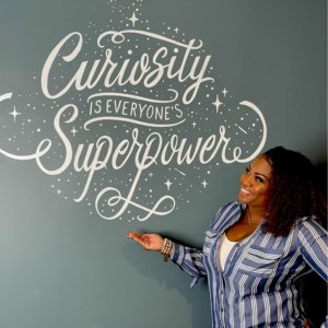 """Shonnah Hughes with sign stating """"Curiosity is everyones superpower"""""""